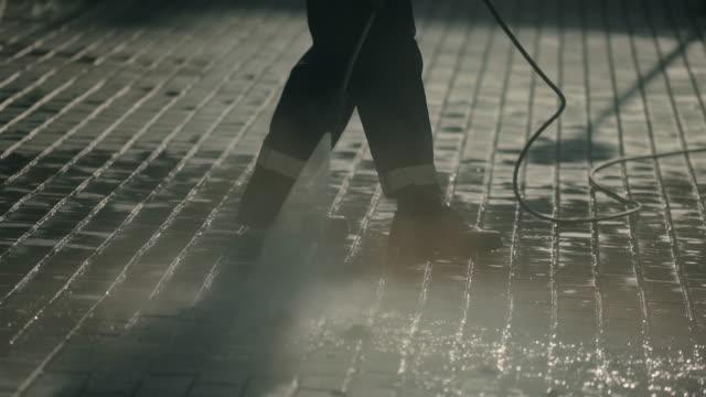 City man clean dirt asphalt brick closeup hosing with powerful jet water 4K