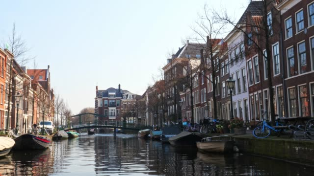 . City of Leiden with his canals in early morning sun. Shot from the water, Canals with historical houses in the dutch city of Leiden. Birthplace of Rembrandt van Rijn. dutch architecture stock videos & royalty-free footage