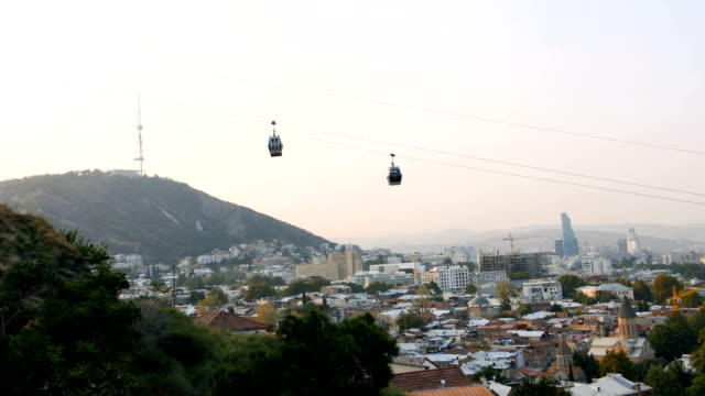 City of Tbilisi gets lively and busy in the morning, Georgia, cabins coming up by ropeway video
