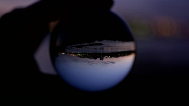 City reflecting in glass ball. Sunset