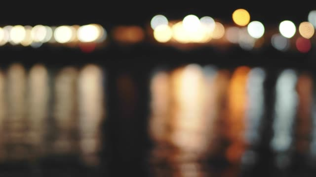 city seaport at night. sea surface. reflection of bright spotlights on the water surface. quiet ripples. bokeh float lights - jesus christ filmów i materiałów b-roll