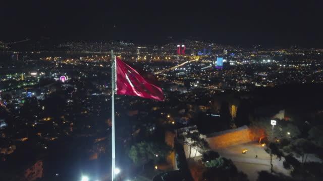 vídeos y material grabado en eventos de stock de horizonte de la ciudad dibujado por zángano de la noche, bandera de skyline la ciudad delante de kadifekale, izmir - material de construcción