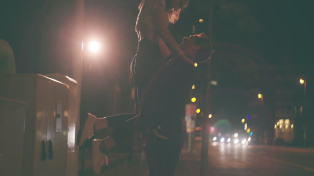 City street at night with loving couple on a date Wide angle shot of a late night city street with a loving young couple who are out on a date with the guy lifting up his girlfriend in a loving and playful way human relationship stock videos & royalty-free footage