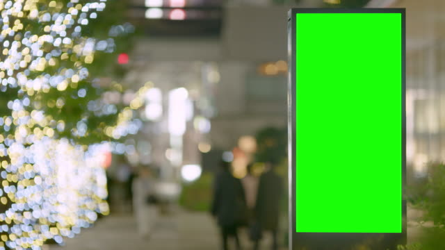 городская улица billboard стенд с зеленым экраном столицы в ночное время. медленное движение с пассажирами, людьми и зимними огнями на деревьях. - коммерческий знак стоковые видео и кадры b-roll