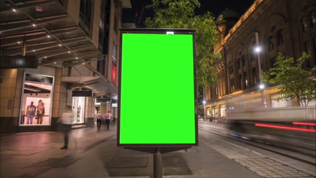vídeos de stock e filmes b-roll de city street billboard stand with green screen. time lapse with commuters, people and cars. space for text or copy. - faixa sinal