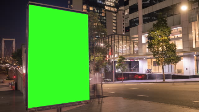 stadt straße billboard stand mit grünem bildschirm. zeitraffer mit pendlern, menschen und autos. leertaste für text oder kopie. - schlüssel videos stock-videos und b-roll-filmmaterial