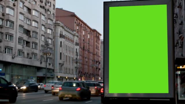 vídeos y material grabado en eventos de stock de calle de la ciudad. noche. escaparate con una gran pantalla verde. vienen autos. - póster