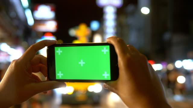 vídeos y material grabado en eventos de stock de calle de la ciudad: mano pantalla verde - póster