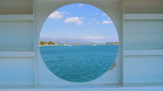 City summer landscape view of Greece seen from inside a ship cabin with round peep-hole window. Round window in a shabby wall with brush marks and a sea view clipping path included