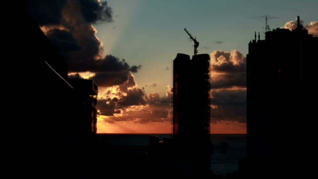 City sunset timelapse Timelapse of Sunset over city of Beirut, Lebanon. Thick cumulus clouds are lit by the setting Sun which appears behind the building just as it starts disappearing into the sea. beirut stock videos & royalty-free footage