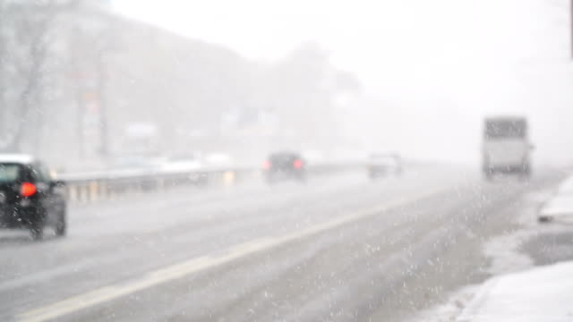 City traffic during winter snowfall, slippery road conditions, risk of accident