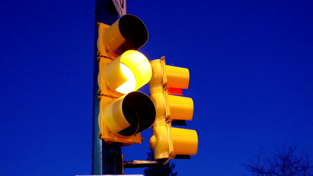 City traffic light turns from green to red against blue sky video