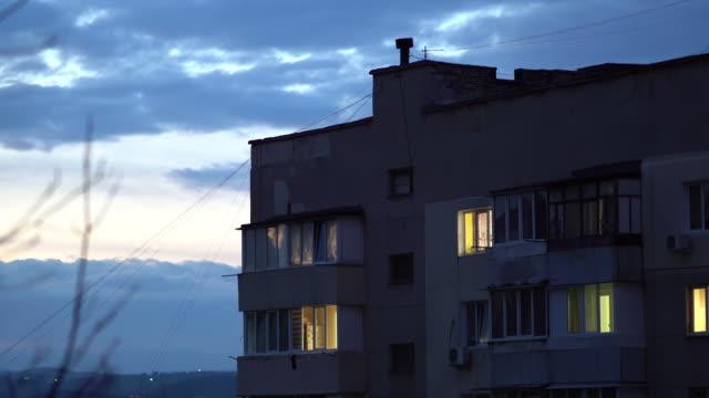 scena crepuscolare della città, finestre di condominio residenziale al crepuscolo - ambientazione esterna video stock e b–roll