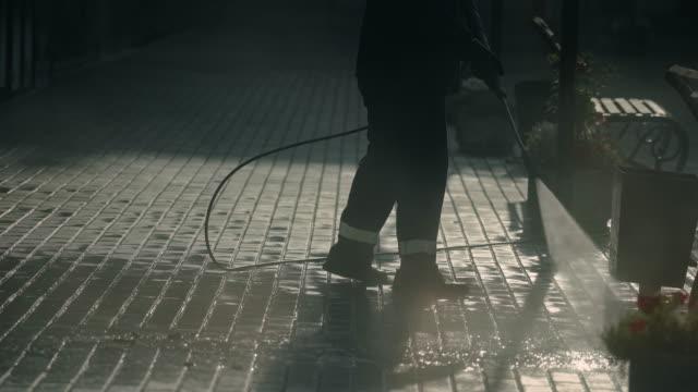 city worker clean sidewalk brick block closeup hosing with powerful jet water 4k - tubo flessibile video stock e b–roll