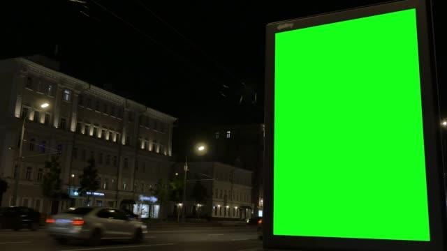vídeos y material grabado en eventos de stock de caja de luz de la ciudad se encuentra en la calle contra los edificios por la noche - tablón