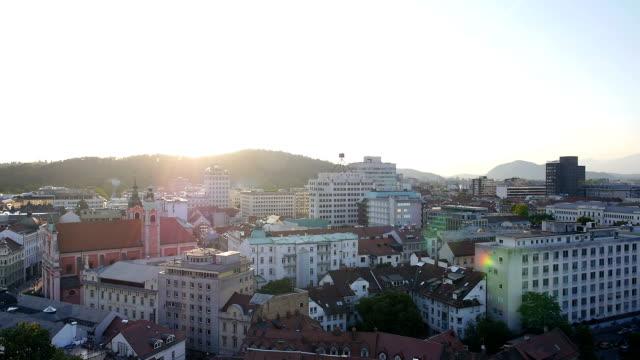 aerial: cityscape bathing in the sun - walking home sunset street bildbanksvideor och videomaterial från bakom kulisserna