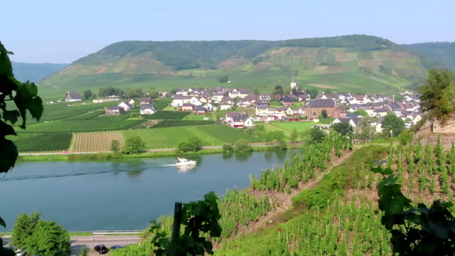 cityscape of Ellenz at Moselle River with motorboat passing by on river.