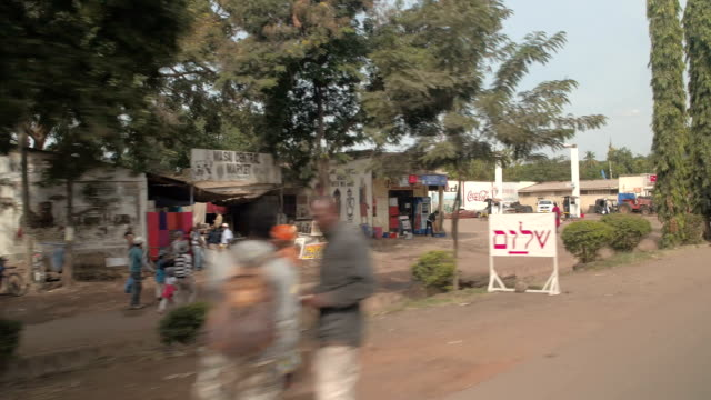 CLOSE UP: Cityscape of poor African village, colorful marketplaces and workshops KARATU, TANZANIA - JUNE 10, 2016: Driving along filthy but picturesque African town. Residents riding bikes, working in small market places, cargo delivering and hanging out on dirty streets od Africa tanzania stock videos & royalty-free footage