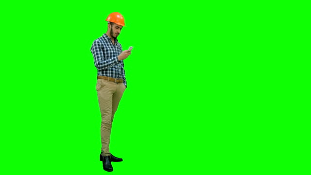 Civil engineer in helmet using mobile phone on a Green Screen, Chroma Key video