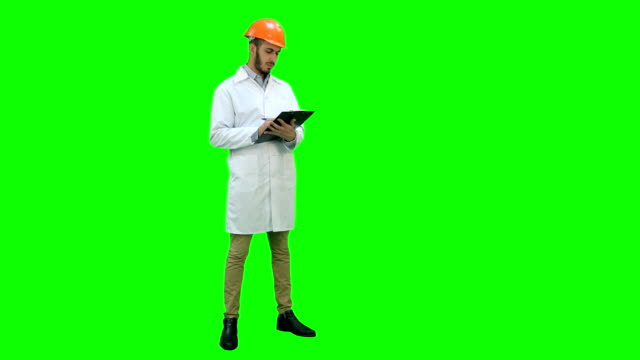 Civil engineer in white coat preparing report on a Green Screen, Chroma Key Civil engineer in white coat preparing report. Professional shot on a Green Screen, Chroma Key on Lumix GH4 in 4K resolution. You can use it e.g. in your commercial video, business, presentation, broadcast video. full length stock videos & royalty-free footage