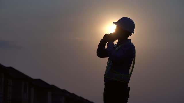 現場の土木技師検査棟と電話を現場で - クレーン点の映像素材/bロール