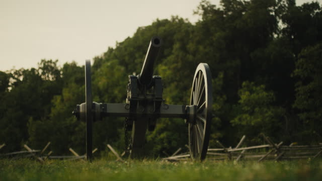 A US Civil War Cannon from Gettysburg National Military Park, Pennsylvania at Sunset in a Grassy Area next to a Forest and a Wooden Fence