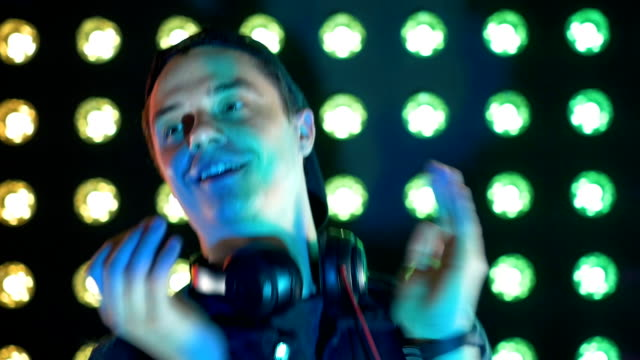 A DJ claps his hands and dances to music. video