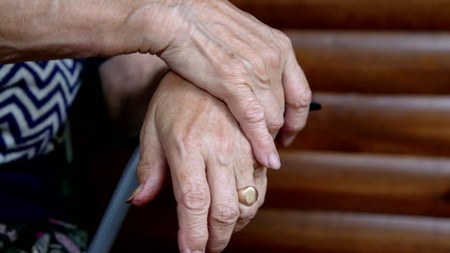 Clasped senior woman hands video