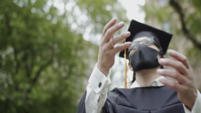 vídeos de stock e filmes b-roll de class of 2020 graduate wearing protective mask and graduation gown and mask - comemoração conceito