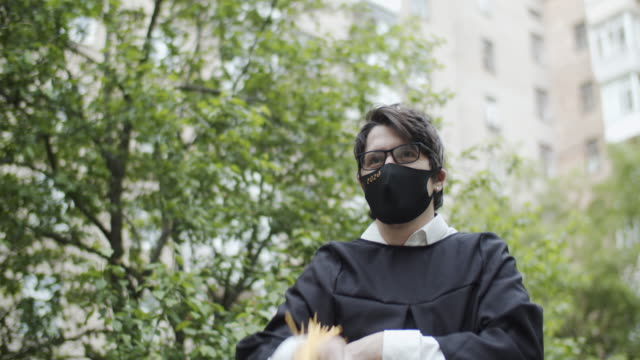 Class of 2020 graduate wearing protective mask and graduation gown and mask