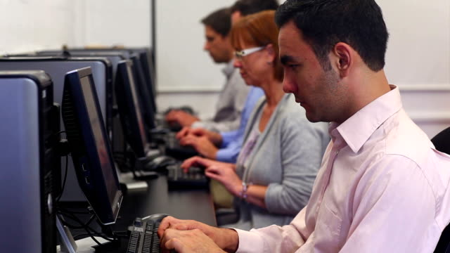Class of mature students working in computer class video