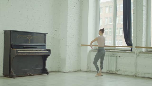 klassisk balettdansare utövar demi plattång på barre - balettstång bildbanksvideor och videomaterial från bakom kulisserna