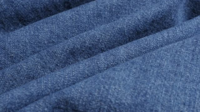 Classic blue denim surface gathers close-up 4K Classic blue denim surface gathers close-up 4K 2160p 30fps UltraHD tilting footage - High quality jeans texture details slow tilt shallow DOF 3840X2160 UHD video fabric swatch stock videos & royalty-free footage