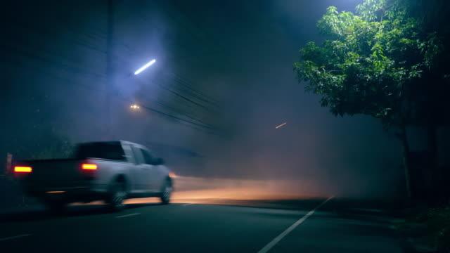 stockvideo's en b-roll-footage met klassieke autoaandrijving in verlaten weg met grote groep rook en spookstadconcept - mist donker auto