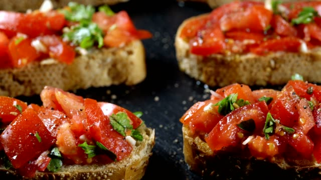vídeos de stock, filmes e b-roll de bruschetta italiana clássica, tomate, alho e salsa no pão torrado - antepasto