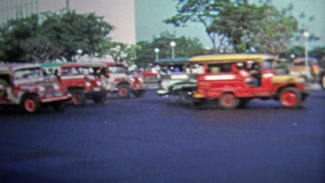 1973: Classic Jeepney driving past busy urban intersection. video
