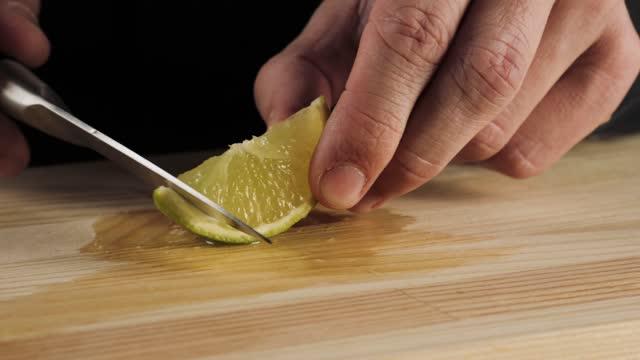 классический коктейль маргарита. бармен берет стальной нож и зеленую известь и отрезает кусок свежей лайма для украшения. концепция подгот - лимонный сок стоковые видео и кадры b-roll