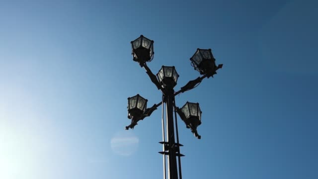 classic older lamp and blue sky. old fashioned street light against a blue sky. vintage style street lights by the day. footage - victorian architecture stock videos & royalty-free footage