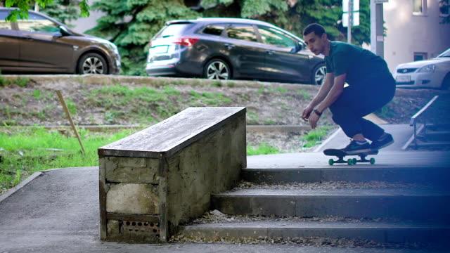 古典的なスケートボーダーのスタント。コンクリート塀にジャンプして若いスケートボーダー - 階段点の映像素材/bロール