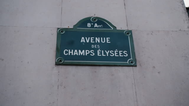 classic street sign of avenue champs elysees or elysian fields located on a house in paris. france. shot with parallax effect relative to houses in the background. illustration of shopping and expensive shops on avenue des champs-élysées - paris fashion stock videos & royalty-free footage