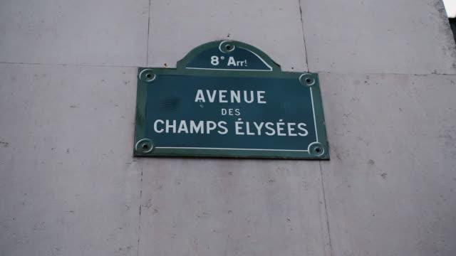 vídeos de stock, filmes e b-roll de sinal de rua clássico da avenida champs elysees ou dos campos de elysian situados em uma casa em paris. frança. disparado com efeito do paralaxe relativo às casas no fundo. ilustração de compras e lojas caras na avenue des champs-élysées - moda parisiense