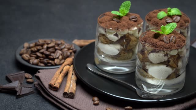 classic tiramisu dessert in a glass on dark concrete background - theobroma video stock e b–roll