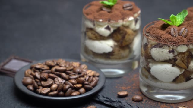 classic tiramisu dessert in a glass on stone serving board on dark concrete background - theobroma video stock e b–roll