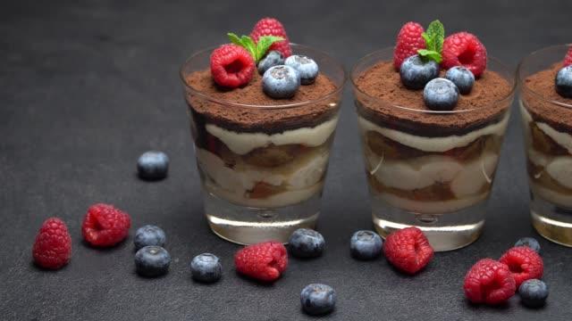 classic tiramisu dessert with blueberries and raspberries in a glass on dark concrete background - theobroma video stock e b–roll