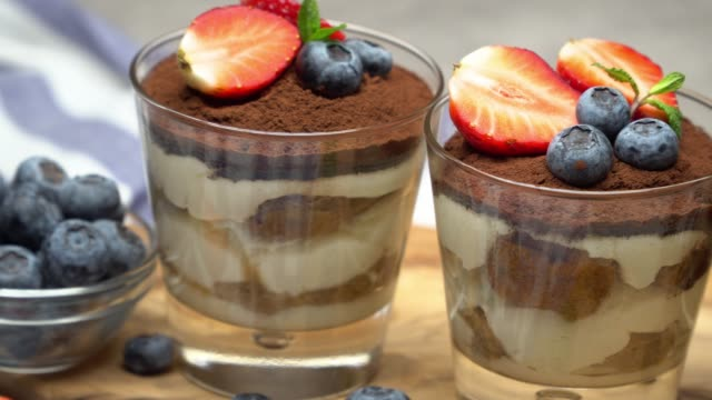 classic tiramisu dessert with blueberries and strawberries in a glass on concrete background - theobroma video stock e b–roll