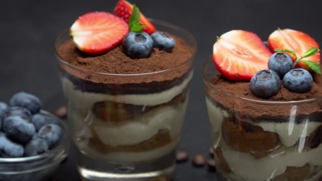 classic tiramisu dessert with blueberries and strawberries in a glass on dark concrete background - theobroma video stock e b–roll