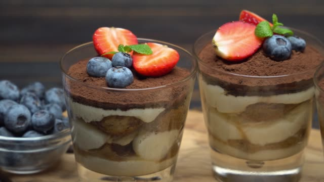 classic tiramisu dessert with blueberries and strawberries in a glass on wooden background - theobroma video stock e b–roll