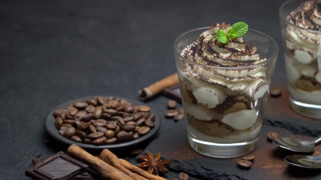 classic tiramisu dessert with blueberries and strawberries in a glass on stone serving board - theobroma video stock e b–roll
