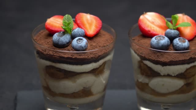 classic tiramisu dessert with blueberries and strawberries on stone serving board on concrete - theobroma video stock e b–roll