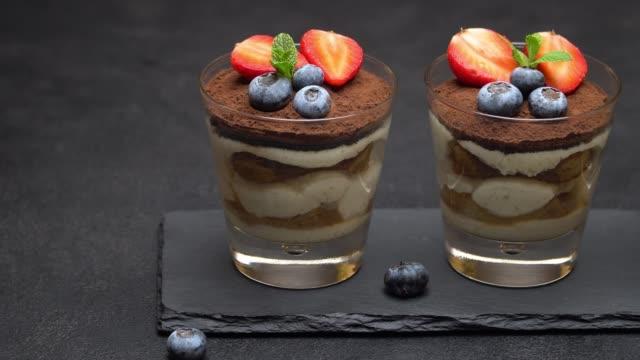 classico dessert al tiramisù con mirtilli e fragole su tavola da portata in pietra su cemento - theobroma video stock e b–roll